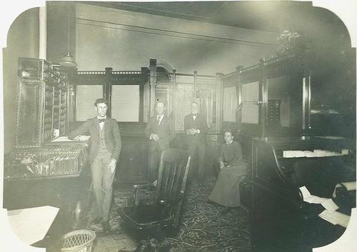 Interior of the Land Records Office in the State Capitol building with 2 of 4 staff in the photograph identified as George G. Brown, Deputy, and Julia K. Webster., Courtesy of Oregon State Library