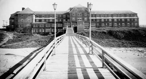 View from the end of the wooden walkway leading to the edge of beach, looking back toward Hotel Gearhart building. Light posts and railings of the walkway are visible., Courtesy of Oregon State Library