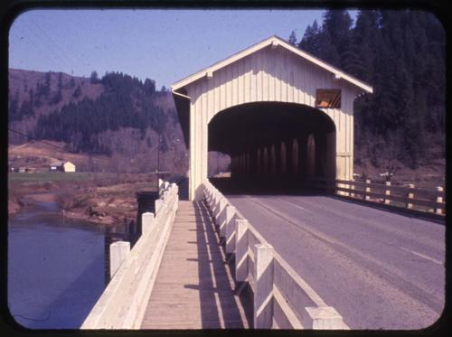 Mapleton bridge in Mapleton, Oregon, over Siuslaw River is a Howe covered bridge built in 1934. The two spans are 105 feet each with approaches and a 35 foot draw, totally nearly 650 feet in combined length. Location: T18S R10W S2, Photo by Glenn G. Groff., Courtesy of State Library of Oregon.