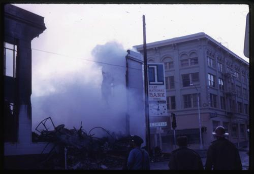 Police and firefighters stand outside of First National Bank of Oregon building damaged by fire in Roseburg, Oregon, Photo by Glenn G. Groff., Courtesy of State Library of Oregon.