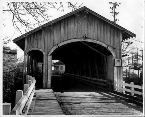 "Bryant Park Covered Bridge in Albany, Oregon. The 130-foot Howe Truss spanned the Calapooia River. The bridge was built circa 1924 and torn down in 1962. Covered spans with pedestrian walks are not uncommon in the East, but few have ever been built in the Far West. In this case, the open-sided pedestrian way accommodated foot traffic to Bryant Park. The Oregon Electric Railroad line passed by the west end of the bridge, and the Albany Ditch dropped into the Calapooia River near the east portal., ""Bryant Park Bridge at Albany was within the city's corporate limits and was the only known Covered Bridge in Oregon to have a separate walk and entrance for pedestrians.""--back of photograph., Courtesy of State Library of Oregon."