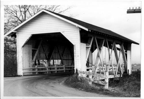 The Bohemian Hall covered bridge near Albany, Oregon. The Howe truss, aluminium-sheeted structure was built in 1947 to replace the earlier bridge that was washed out by a flood. The construction costs totaled $30,000. The 132-foot bridge was 4 miles southeast of Scio on Richardson Gap Road, spanning Crabtree Creek in Linn County, Oregon. The bridge was named for nearby Bohemia Hall which was built about 1922 by the Czechoslovakian community that settled in the area. In 1987 the bridge was dismantled and was to be rebuilt in Timber Linn Park at Albany. However, the timbers of the Howe truss rotted and plans to rebuild the bridge were dropped., Courtesy of State Library of Oregon.