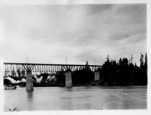 Wilsonville Railroad Bridge over Willamette River in Wilsonville, Oregon. Unidentified steamboat in background., Courtesy of State Library of Oregon.