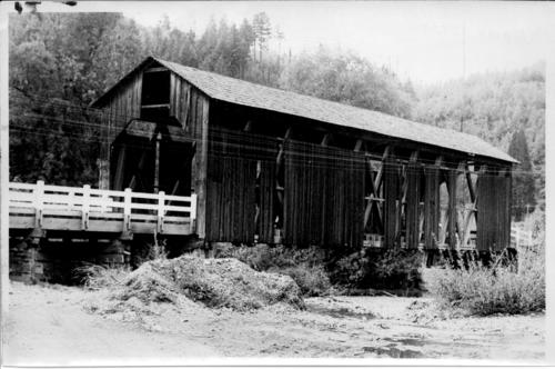 Coleman covered bridge over Abiqua River in Marion County, Oregon, southeast of Scotts Mills. The wooden construction was built in 1925 and costs totaled $2,600. This Howe truss was 16 feet wide, 70 feet long and had a 6-ton-load capacity for traffic., Courtesy of State Library of Oregon.