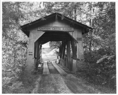 "Canyon Creek Ranch covered bridge is a 75 foot modified queenpost covered bridge built in c1932 by Gale S. Hill, spanning the South Santiam River, and located 1 1/2 miles east of Cascadia near the South Santiam Highway.  Probably no other Oregon covered bridge appears to grow, rootlike, out of its site quite so well as this private span. Gale S. Hill, once district attorney, kept a mountain ""ranch"" for a botanical garden. Hill had the bridge built to serve his ranch. The bridge was destroyed soon after the flood in 1964., Courtesy of State Library of Oregon."
