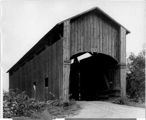 Fox covered bridge spanning the North Coquille River near Norway, Coos County, Oregon. Supported by a Smith truss, the bridge was built in 1883 by J.D. Bennett, a local carpenter, who built several other covered bridges in the county. The old bridge was a victim of a fire in the early 1950s, which also burned the tiny Lee Valley church. Remains of the bridge were dismantled in 1954 and a modern concrete bridge spans the stream., Courtesy of State Library of Oregon.