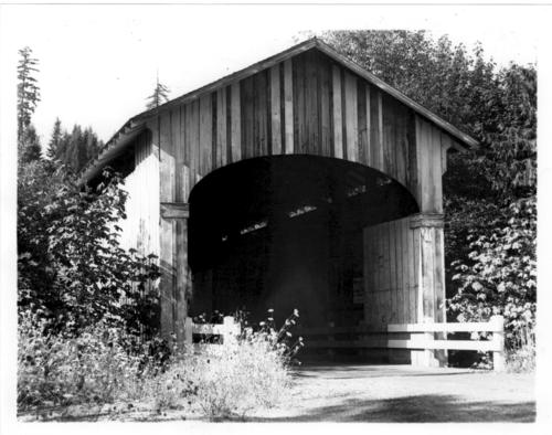 "Wendling covered bridge is a 60 foot Howe truss bridge spanning Mill Creek near Marcola in Lane County, Oregon. The bridge got its name from George X. Wendling, director of the Booth-Kelly Lumber Company. When this photograph was taken, there were several signs inside including a Barnes and Beatty's Circus sign and one near the entrance that reads: ""Wendling Bridge built by Lane Co - 1938 A.C. Stricker - Bridge Supt. No. 16-1W-10."" Location: T16S R1W S10., Courtesy of State Library of Oregon."