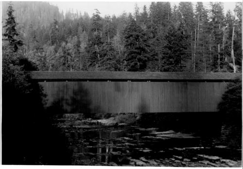 Swisshome covered bridge over Lake Creek in Lane County, Oregon, is a 180 foot Howe truss design built in 1919. The bridge was replaced in the early 1960s., Courtesy of State Library of Oregon.
