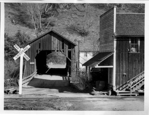 Covered bridge in Chitwood, Oregon, over Yaquina River next to the Chitwood Store, c1955., Courtesy of State Library of Oregon.
