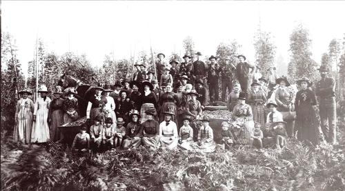 Hop pickers at Berry's hop yard in Fox Valley, east of Lyons, Oregon. 5th from L, standing, Mrs. Hamilton; Mrs. Stoessel sitting at R of hop box; sitting at L corner of hop box, Josephine (S) and Valerine (R) Stoessel. Standing high, 1st on R, Andy Siegmund (has watch chain with charm); 2nd to R of hop box, standing, Mrs. Martha Berry, wife of owner, Preston Berry--has on plaid skirt. Will Brotherton at L standing high, back row, holding pole. 45 people are unidentified., Courtesy of Oregon State Library