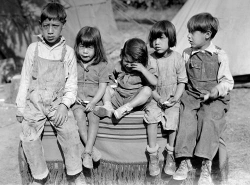 Five young children sitting on a blanket covering a box or bench. The children are dressed in everyday clothing. They probably are the children of hop pickers camped at the hop yard for the picking season. The boy on the left may have been old enough to work with his parents, or could have been the caretaker for the younger siblings while the parents worked., Courtesy of Oregon State Library