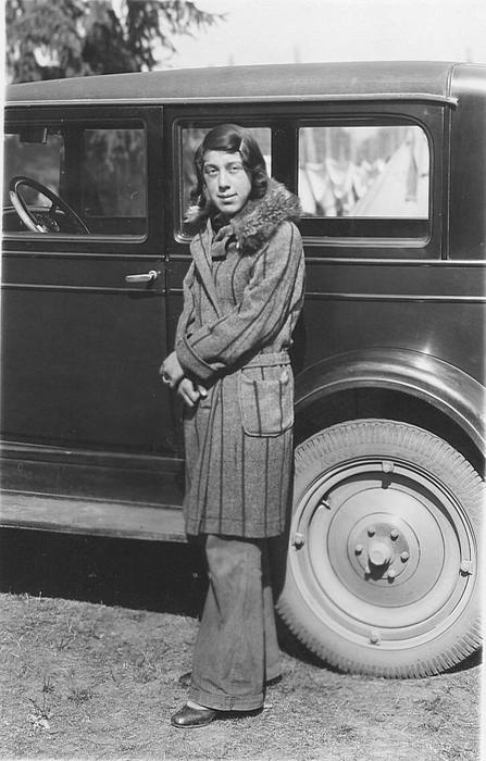 Woman posed by a car in a hop yard. Through the car windows, you can see the line of tents stretching into the distance., Courtesy of Oregon State Library